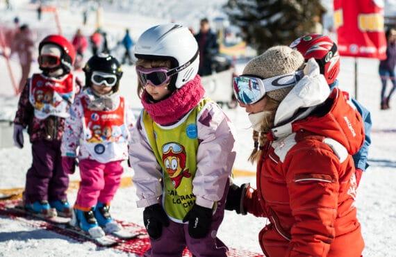 Monitrice de ski qui accompagne l'apprentissage des enfants