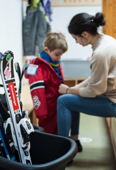 Educatrice qui ferme la veste d'un enfant avec son cours de ski à la Maison des Enfants Saint François Longchamp