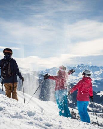 Skieurs sur piste de ski au soleil avec neige fraîche