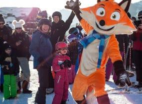 Mascotte renard Goupy avec enfants et familles au ski