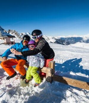 Famille au ski qui se prend en photo avec une belle vue