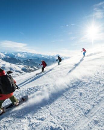 Snowboard et ski sur piste neige et soleil