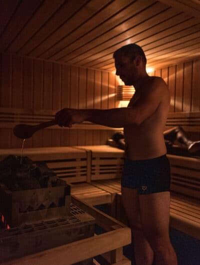 Personne qui ajoute de l'eau dans un sauna
