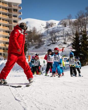 Moniteur de ski avec groupe d'enfant