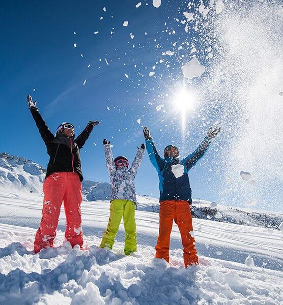Famille heureuse qui joue avec la neige au soleil